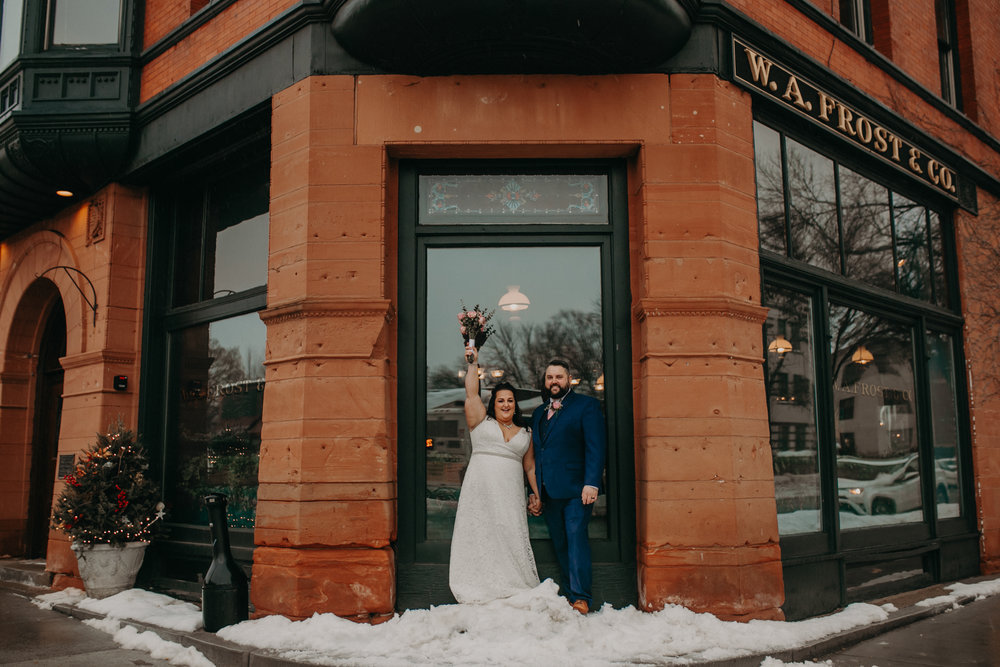 A bride and groom excitedly pose for their first photo as a married couple in front of W.A. Frost