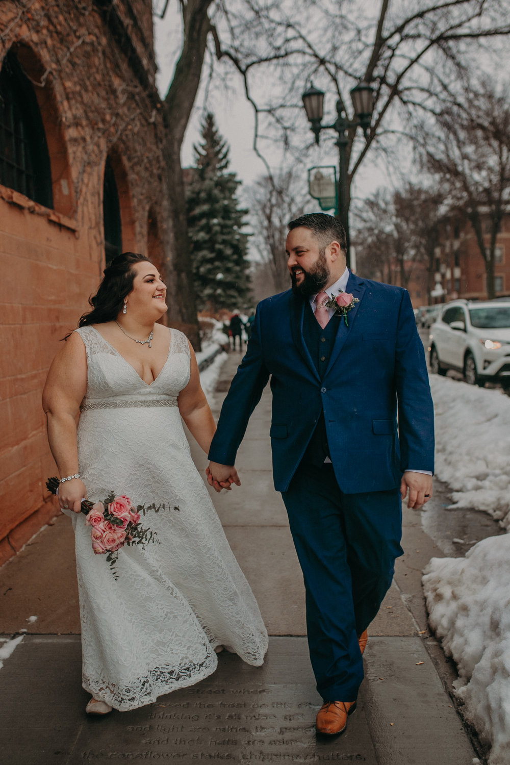 A couple just married stroll along the sidewalk near W.A. Frost on Historic Cathedral Hill in St Paul MN