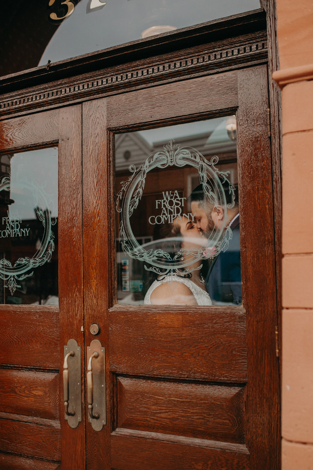 A bride and groom kiss in the doorway and through the window of WA Frost in St Paul MN