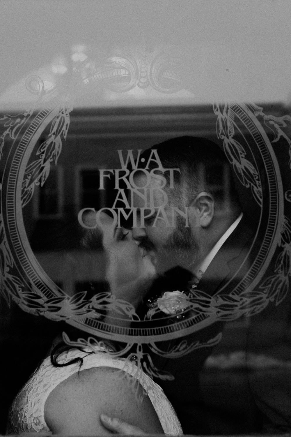 A black and white photo of a married couple kissing at W.A. Frost in the window
