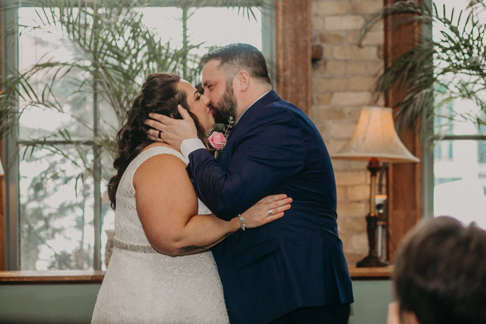 A bride and groom enjoy their first kiss as husband and wife at W. A. Frost in St Paul MN