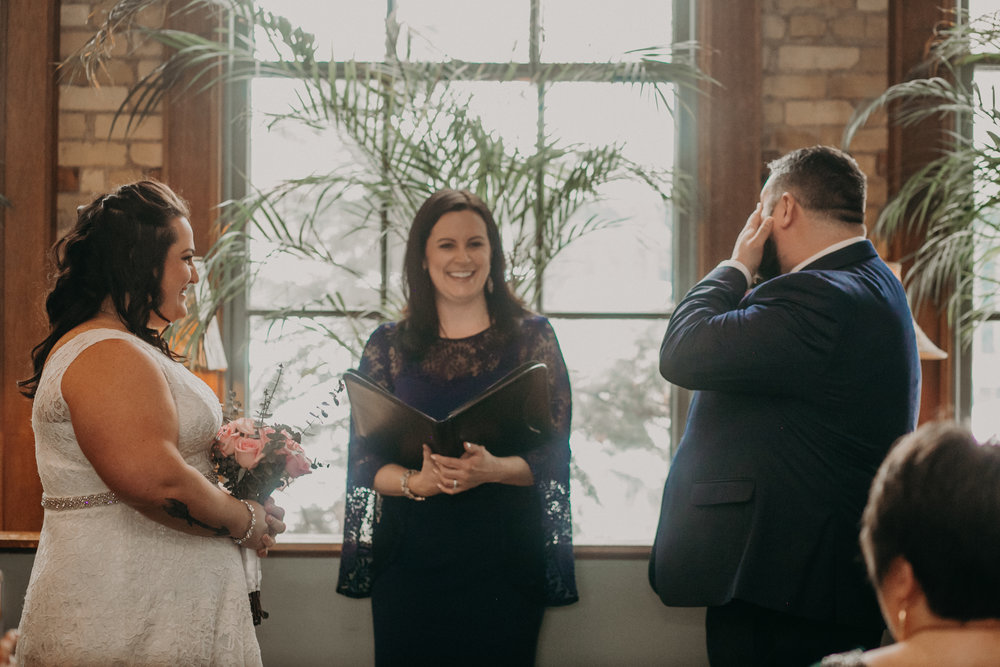 A groom cries seeing his bride for the first time in an intimate non-traditional wedding ceremony at W.A. Frost in St Paul MN