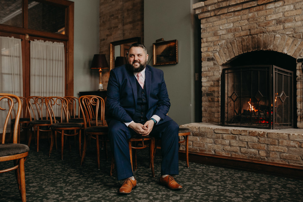 Twin Cities groom poses for his wedding portraits at W.A. Frost Fireside Room before his March wedding