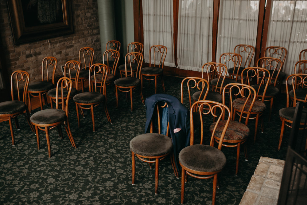 A groom's jacket sitting in the empty Fireside Room at W.A. Frost in St Paul MN before his wedding