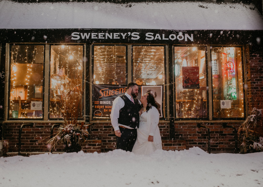 Andrea Wagner Photography captures a couple just married in front of Sweeney's Saloon in St Paul MN during a snow storm winter wonderland