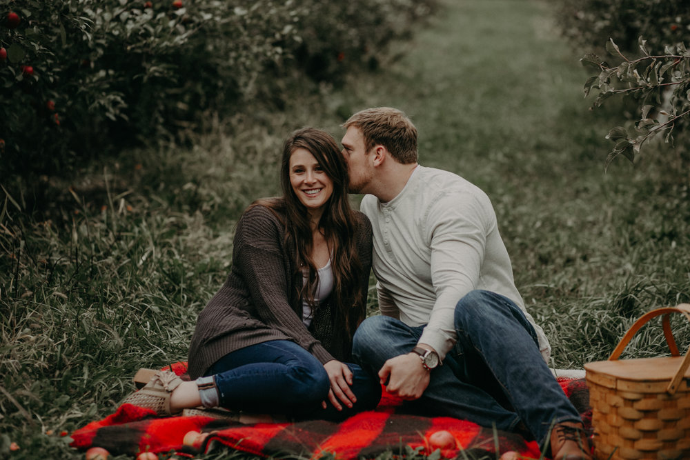 A man whispers into his fiancés ear during their engagement session in Hastings MN with Andrea Wagner Photography