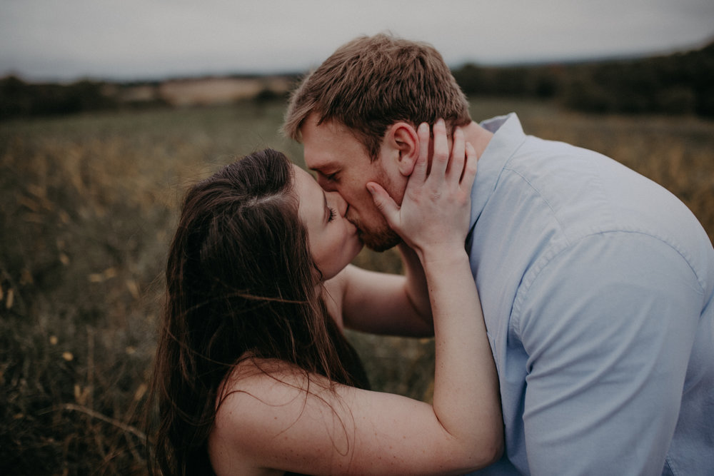A woman in a meadow kisses her fiancé romantically during a Minnesota engagement session