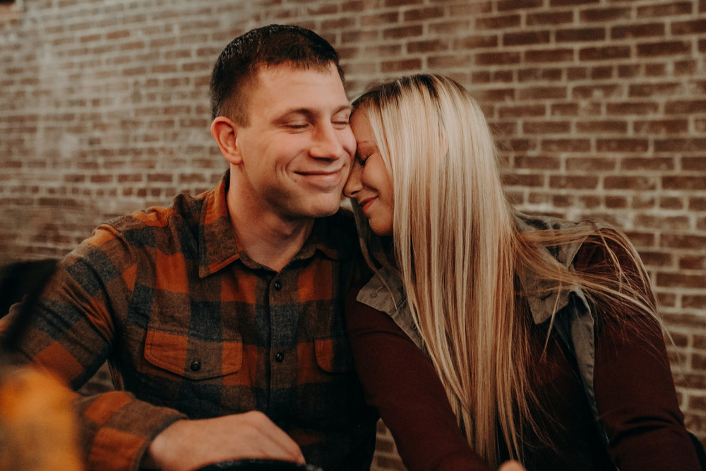 a man smiles while his fiancé snuggles him during an engagement session with Andrea Wagner Photography