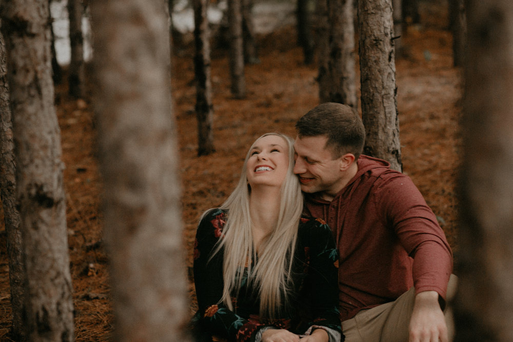 a man makes his fiancé laugh in the forest at Burlap and Bells in Black River Falls WI