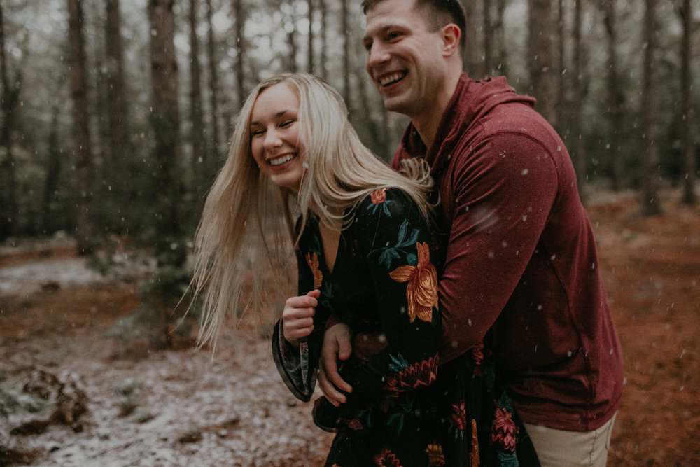 a couple plays and laughs during their engagement session with Andrea Wagner