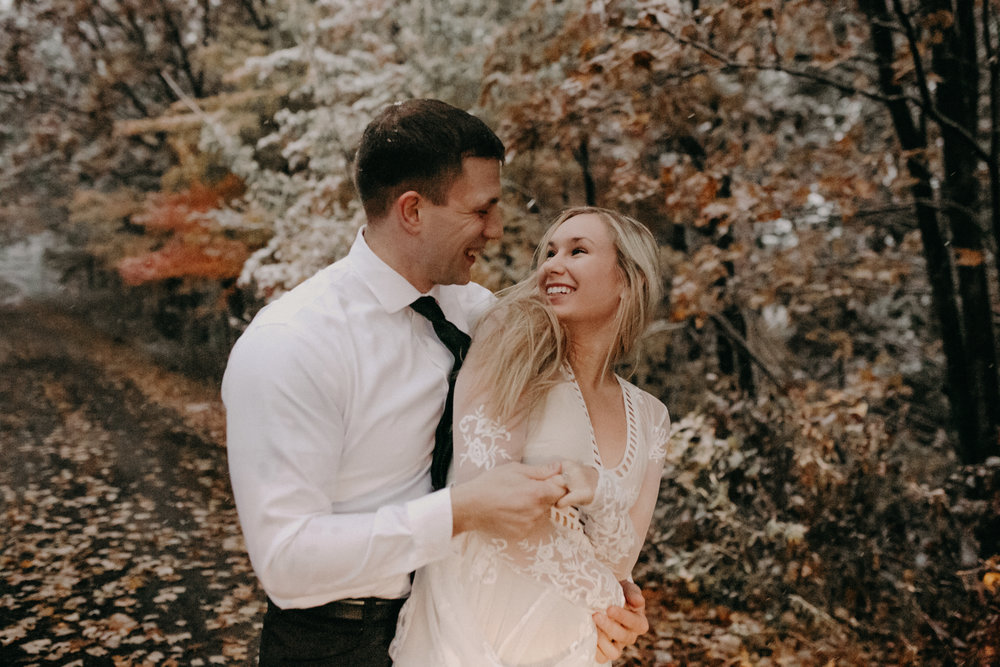 a beautiful happy woman in a lace white dress spins inter her fiancé during their engagement photos in Black River Falls WI