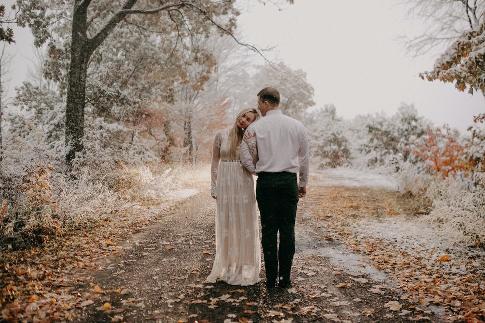 a stunning image captured by Andrea Wagner Photography showing a woman in a white lace dress and a man dressed up holding each other at dusk at Burlap and Bells