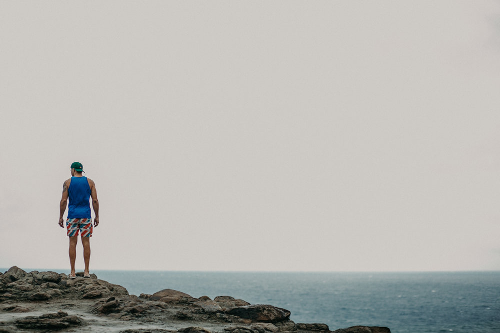 a strong man stands on the cliffs of Hawaii near the Nakalele Blowhole