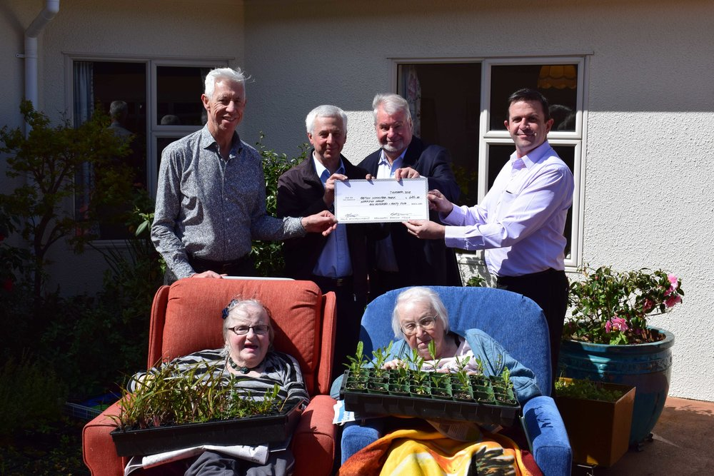 Steve Dunn (Treasurer of the Wellington NZILA Branch – far left) and Michael Wright (Secretary of the Wellington NZILA Branch – far right) present Peter Gilberd (Cashmere volunteer, second from left) and Bruce Patterson (Chairman of the planting group, second from right) and Cashmere Home residents, Therese Shields (front, left) and Shirley (front right), with the cheque to support their planting programme.