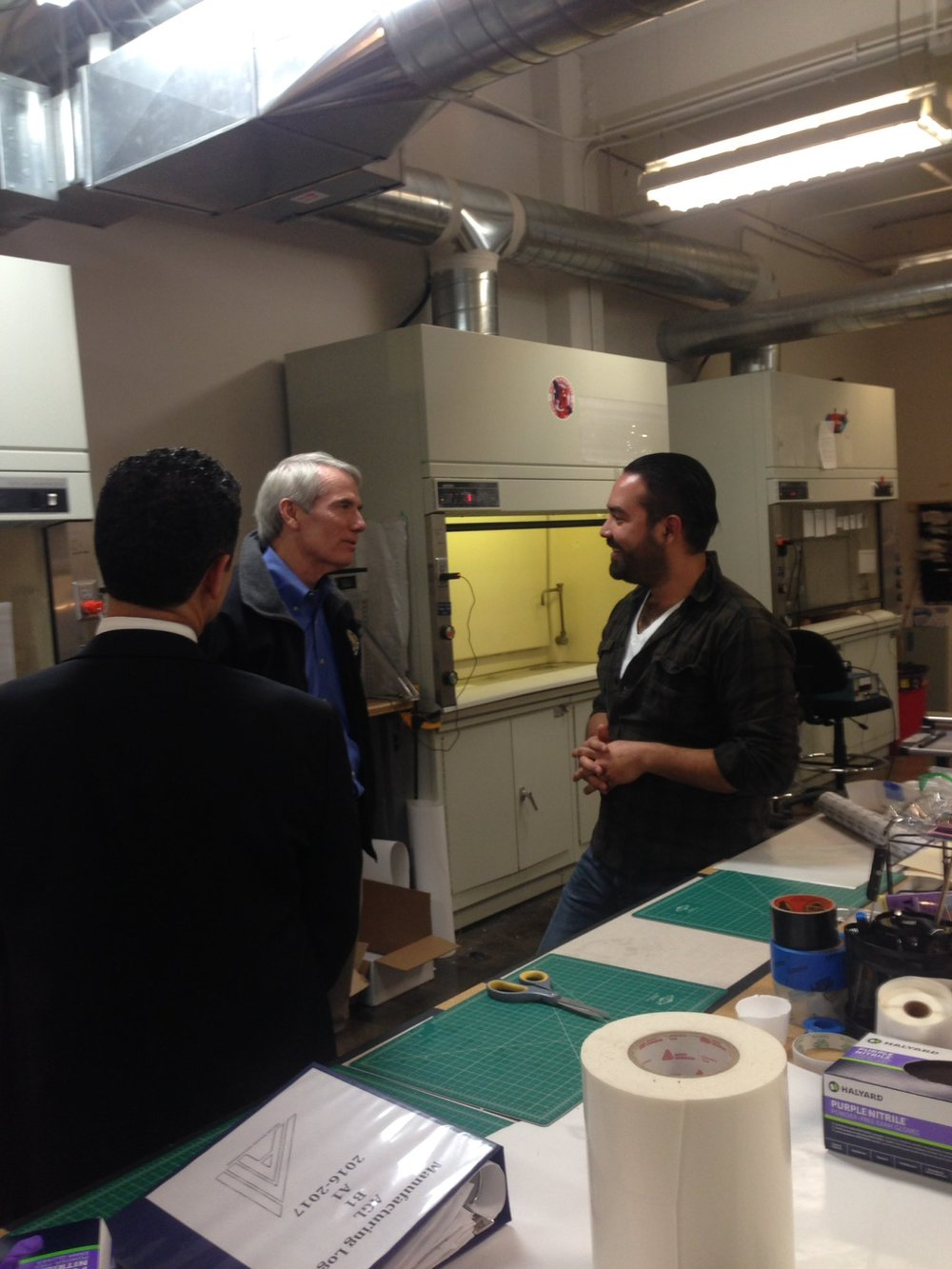 Ali Blandon explaining dry adhesion and electrospinning to Senator Rob Portman and Akron Accelerator CEO Anthony Margida.