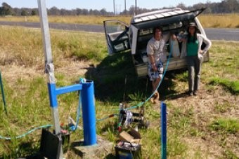 PhD candidate Marnie Atkins (right) testing groundwater bores near Casino with environmental science (Honours) graduate Ben Stewart  .   They are setting baseline data for possible future CSG operations  (Supplied: Southern Cross Uni)