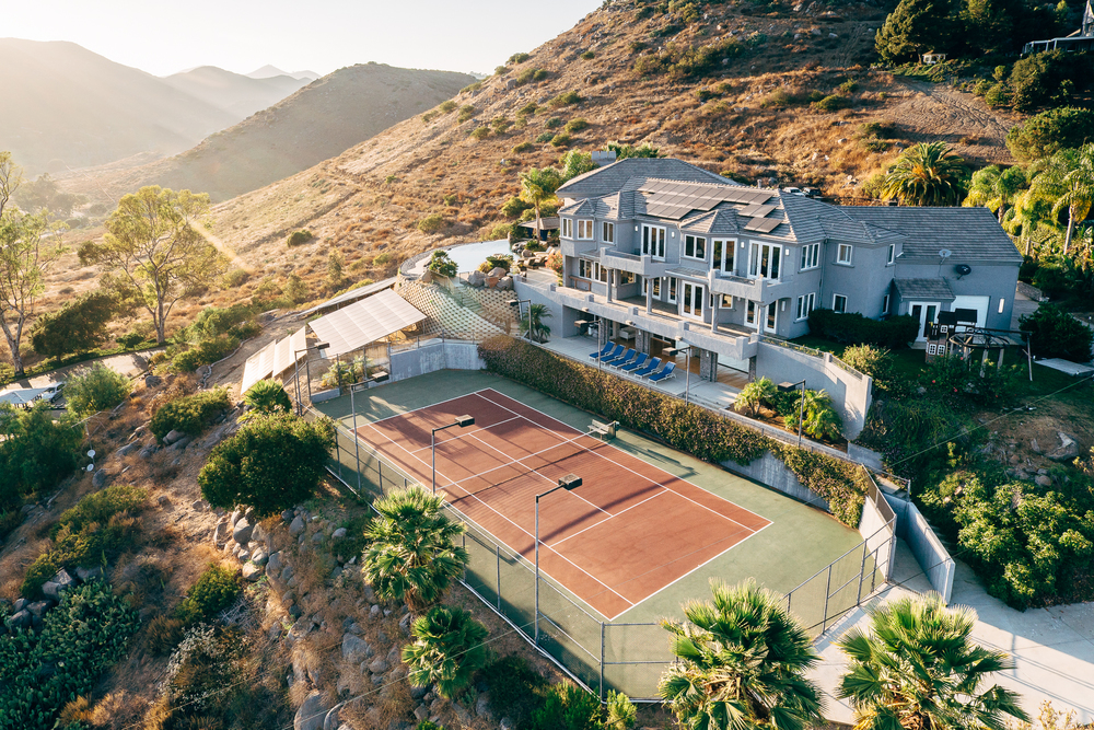 A lighted professional tennis court with 270 degree views sits on the backside of the property and is surrounded by mature palm and fruit trees.