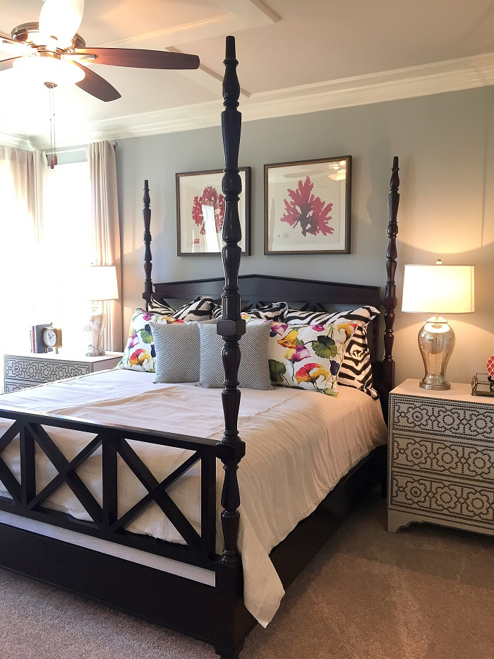 traditional master bedroom, wood poster bed, curtains, framed art, bedside tables, lamps