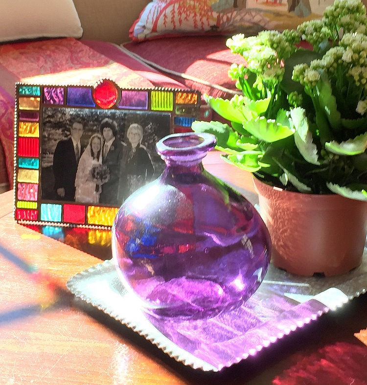 stained glass, picture frame, bottle, plant, leaves, coffee table, tablescape