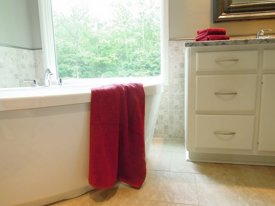 The freestanding tub sits in front of a large--but very private--window,overlooking a pool and beautiful wooded lot.
