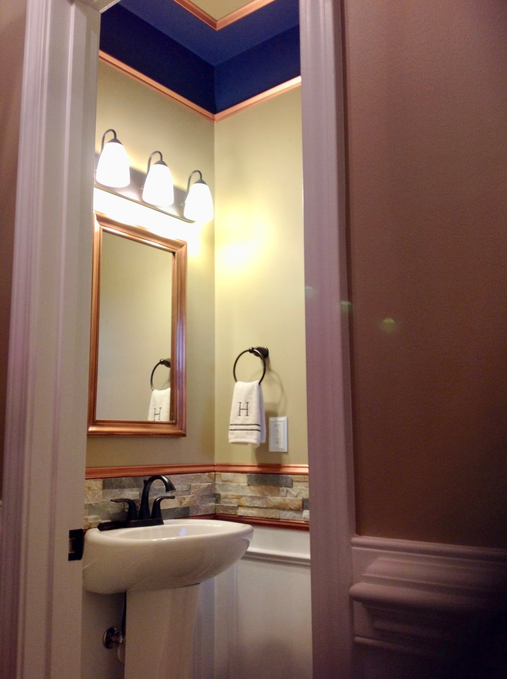 This Powder Room received attention from the floor to the ceiling. Stone tiles! Copper trim! Splashes of color!