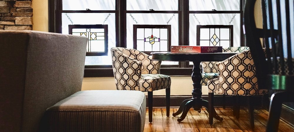 A game table, comfortable chairs and antique stained glass panels in the window create a very special finished basement.