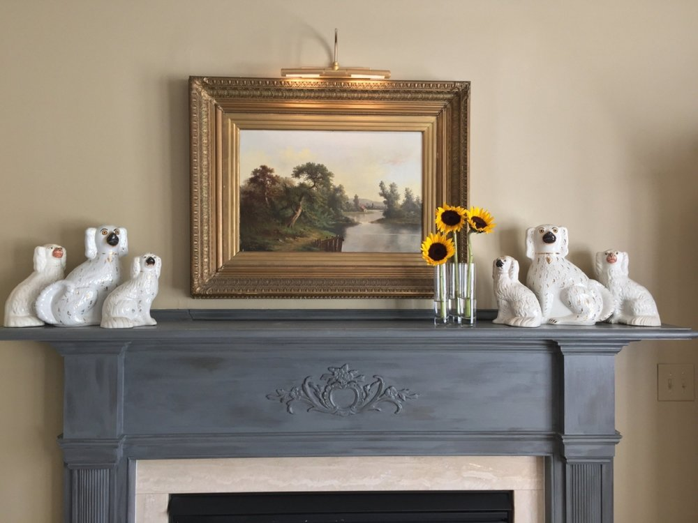 Original artwork and a special collection atop a fireplace mantel with a custom finish, painted by a local artist.