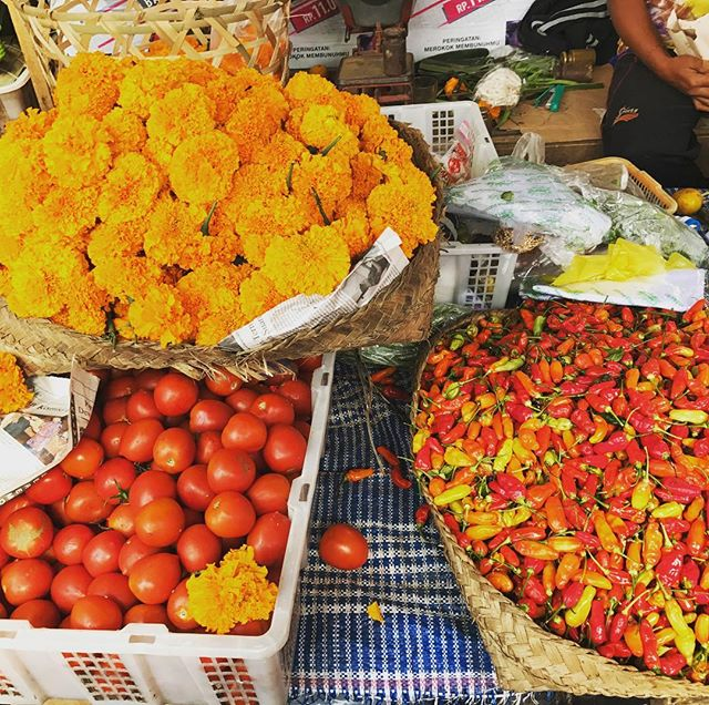 At a local market in Bali. Sacred flowers and spicy chilis 🌶