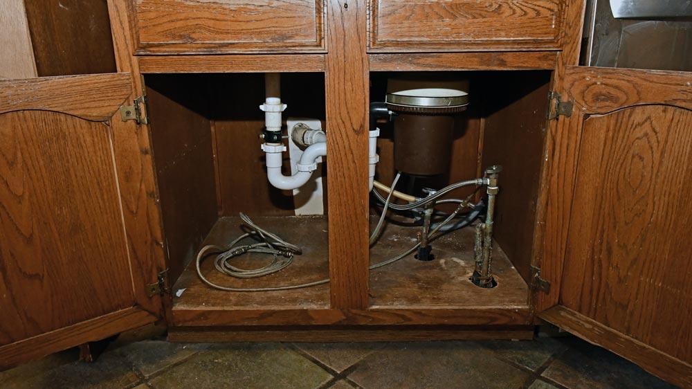 under_sink_plumbing_mess.jpg