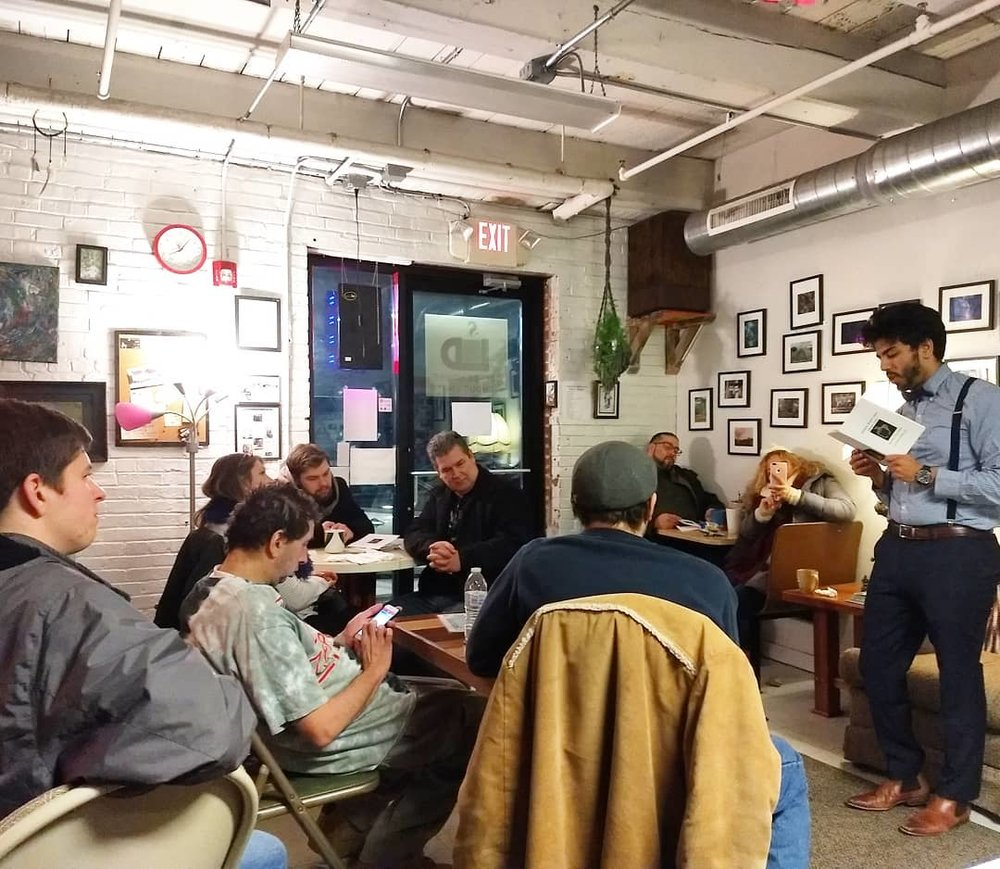 Justin (far right) reads to guests at Coffee House Without Limits in Allentown, PA