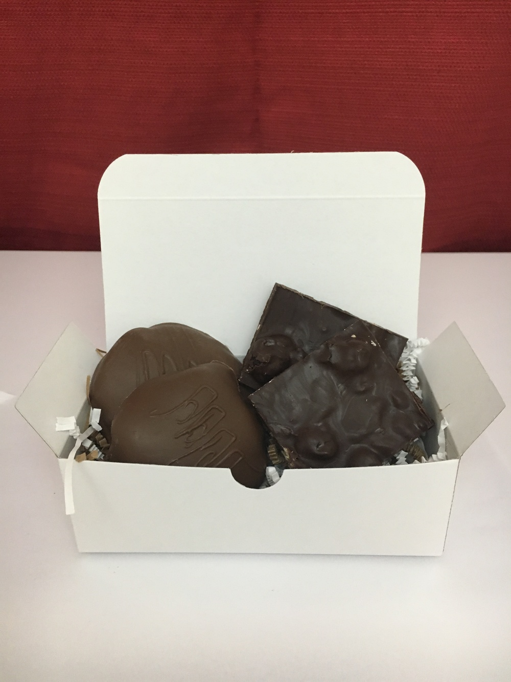 "The 50/50   Can't decide what to order? This 1/2 pound box features Fat Turtle Confections signature treat of 2 ""turtles"" along side dark chocolate bark.  $16.00"