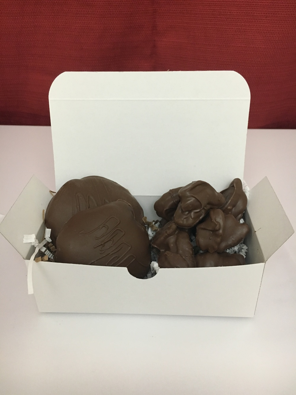 "The 50/50   Can't decide what to order? This 1/2 pound box features Fat Turtle Confections signature treat of 2 ""turtles"" along side chocolate covered pecans (or nuts of your choosing).  $16.00"