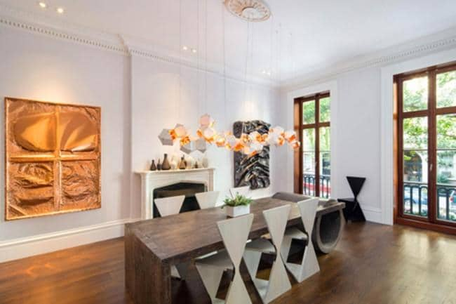 DINING ROOM   The spectacular Greek Revival-style residence features seven fireplaces, one of them comes with a marble mantel. It is also complimented by several striking contemporary installations, like the sculptural pendant lights above the dining table.