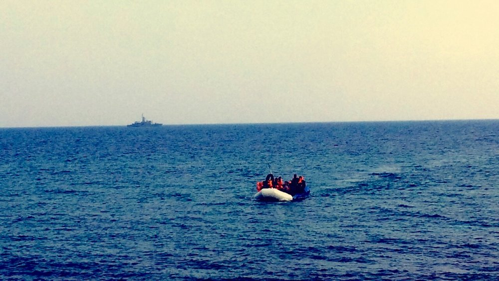 Incoming Refugee Dinghy - Greek coastguard in the distance.