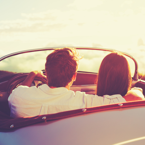 couple embrace in car while looking out into beautiful mountains