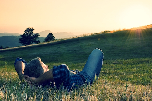 middle aged man looks out at sun laying in field