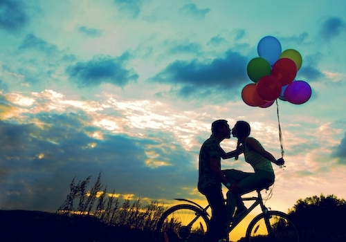 couple kiss on bike with baloons in sunset
