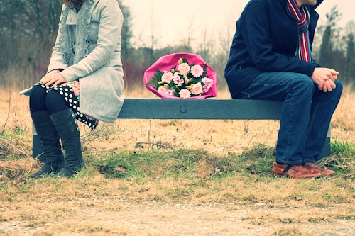 couple site son bench with flowers between them looking away from one another