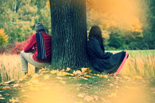 man and woman in park on other side of a tree