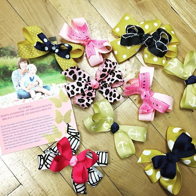 """Marley Bows are here!💙🎀💛 Every October our owner Micaela's family celebrates the life of her sister Polly's daughter, Marley, who was born with Down Syndrome. Marley's signature accessory is a bow. Polly recently finished treatment for Breast Cancer, so we are also celebrating breast cancer awareness month.  We are selling blue & yellow """"MARLEY BOWS"""" for DS Awareness and pink bows for BC Awareness.  We are asking for a $5 donations. ALL proceeds will be used to purchase adult books about Down Syndrome & Cancer for the Grove City Community Library. #downsyndromeawareness #breastcancerawareness #marleybow #findacure #marleymay 💙🎀💛📚"""