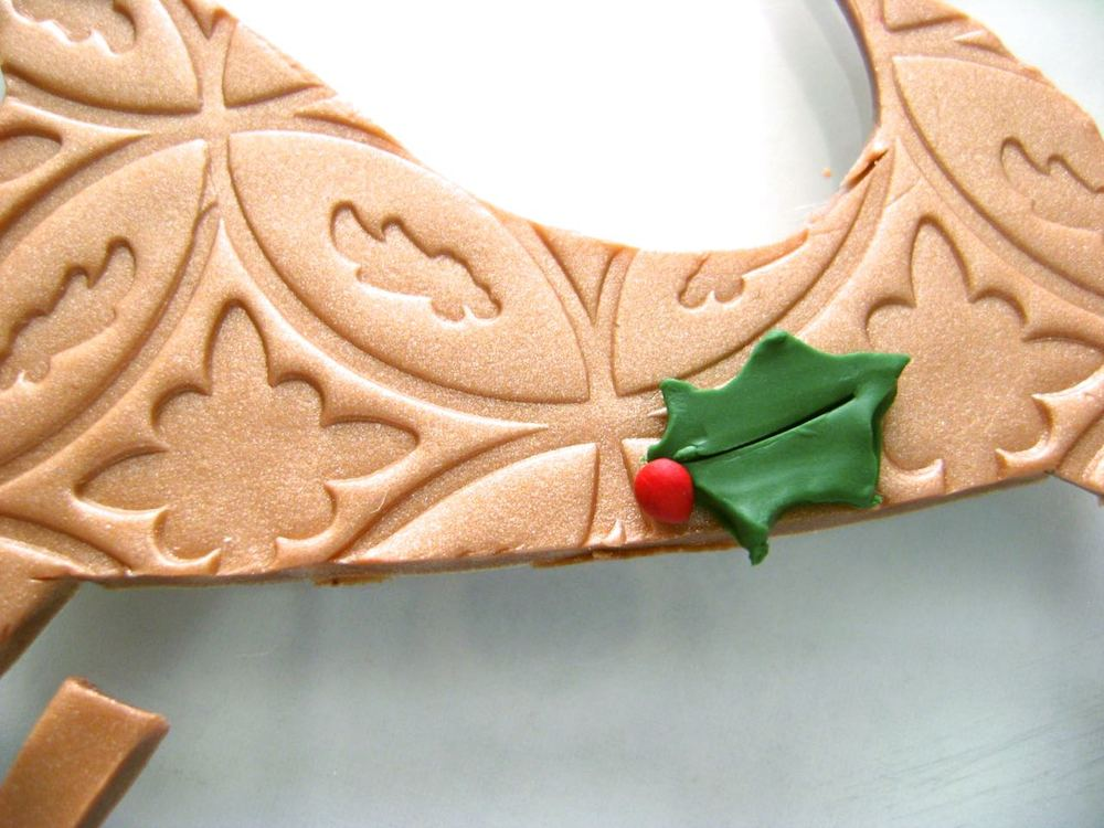 step 5 - Condition and roll out a small piece of green clay and a tiny piece of red clay. Cover the green clay with plastic wrap then cut out two small holly leaves with the craft knife. Roll three tiny pieces of red clay between your fingers to create the berries.  Position the holly and berries at the bottom of the sleigh.