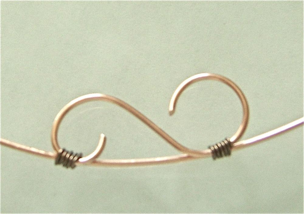 "step 9 - Use 22 gauge copper wire to wrap the decorative ""S"" shape to the center of the runner wire. Hold the pieces together and wrap the thin wire around them 4 times.  Cut off the excess."