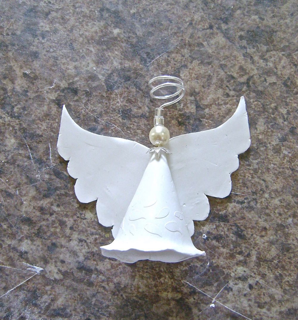 step 9 - Place the wire into the top of the angel.  Pinch the clay around the wire and cover it with the bead cap.