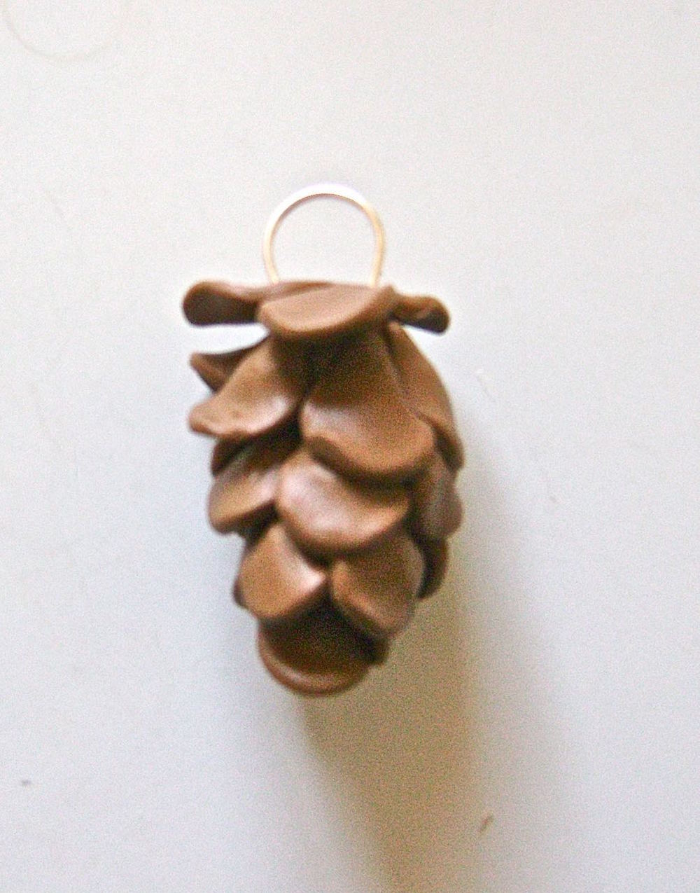 step 7 - Make a hanger by curving a piece of wire around a cylinder, like a marker.  Stick the ends into liquid polymer clay before slipping them into the top of the pine cone.  Handling the wire before the clay is baked will enlarge the holes and cause the wire to fall out so add the wire right before you bake.
