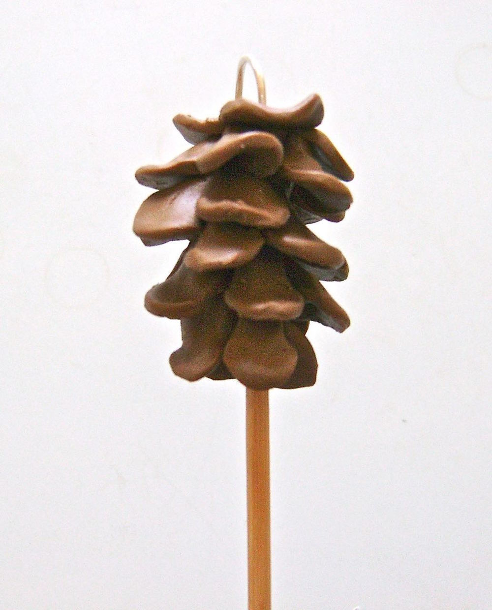 step 8 - Stick the pine cone onto a wood pick to make it easier to work with. Use another pick to lift the pine cone edges away from the teardrop core and give it fullness and shape.