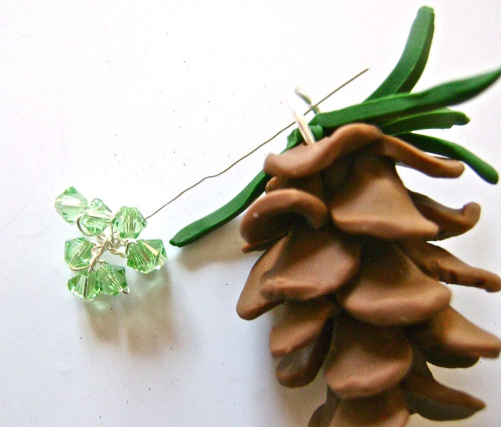 step 12 - Slip the wire ends into the hanger and wrap them around to secure them.  Bend the wires to distribute the beads across the top of the pine cone.