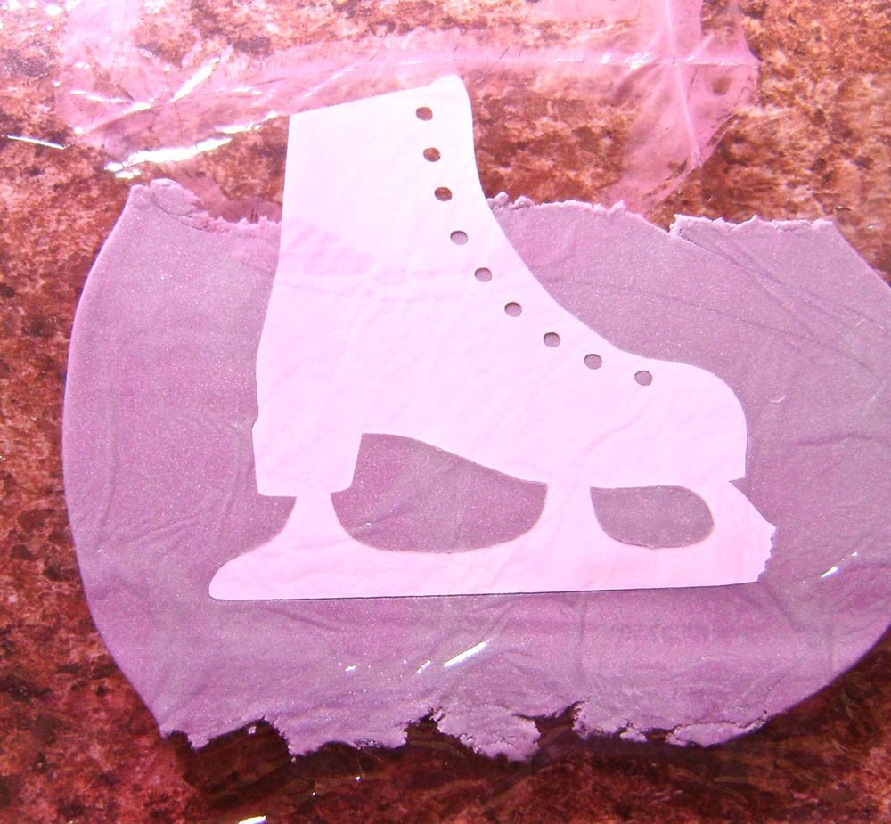"step 3 - Place the stencil on a piece of silver clay flattened to less than 1/8"".  Cover the stencil with plastic wrap."