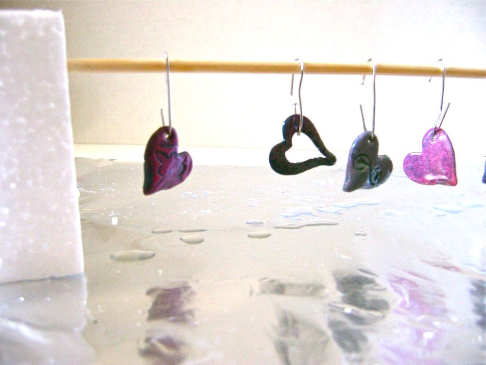 step 12 - Shape small hangers for the hearts and frames with paper clips. Dip each heart in a small container of Diamond Glaze.  Tap off excess and hang the pieces to dry on a wood pick.  Protect the surface beneath.  After about a half hour you'll see a bubble of glaze hanging off each piece.  Remove it by running your finger smoothly against it.  Allow the pieces to dry over night.