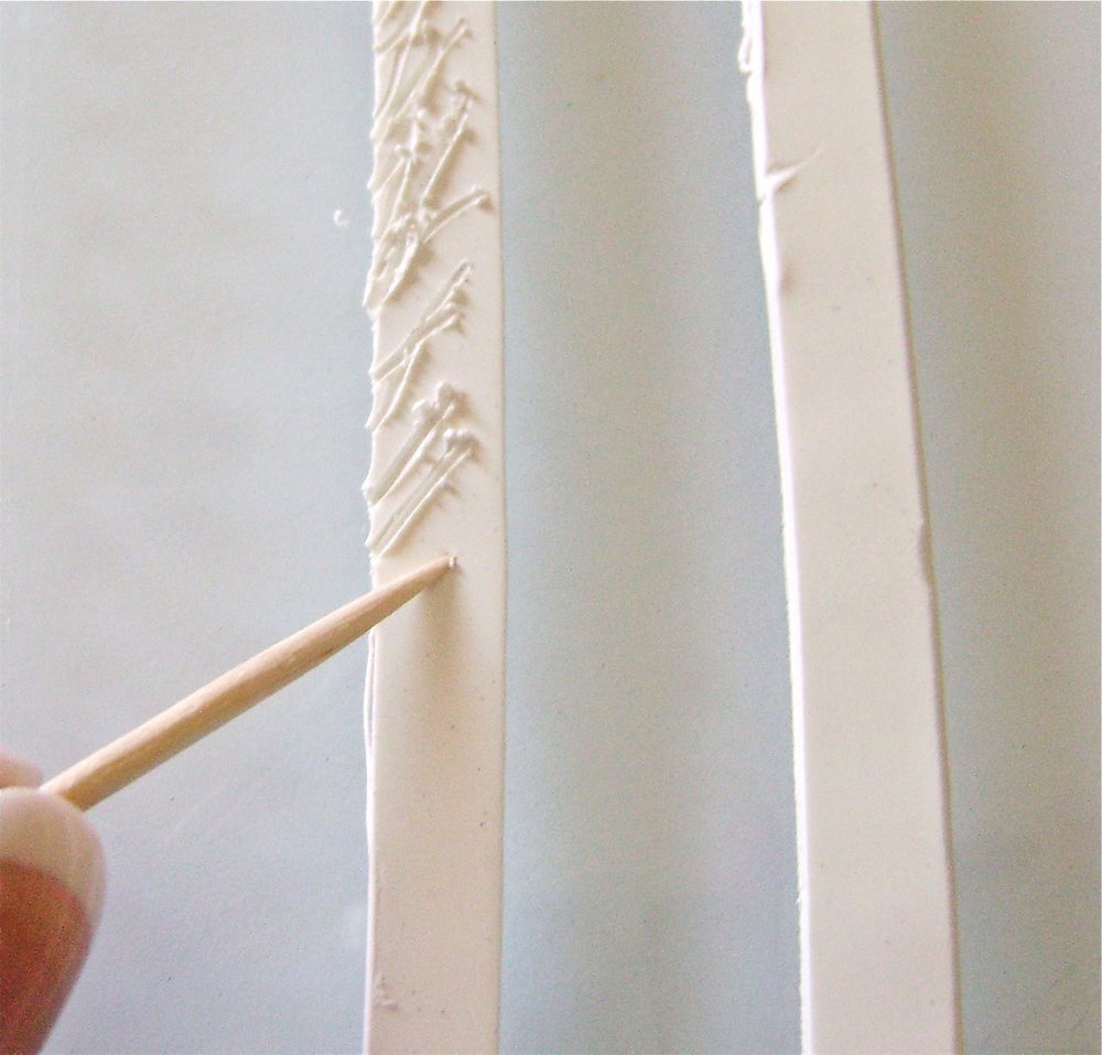 "step 12 - With a blade, cut a 3/8"" wide strip of white clay long enough to reach from the bottom left to the bottom right of the coat following the outer edge.  Use a toothpick to pull at the clay creating a textured fur surface."