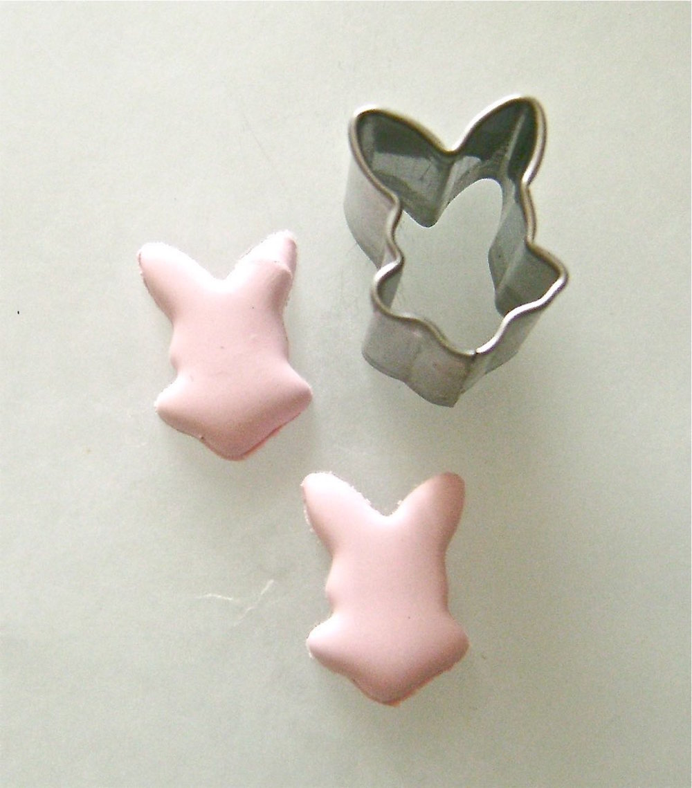 step 6 - Press a bunny cutter onto the pink clay.  Cut out 24 pink pieces and 24 white.  Two bunnies will be joined to create one playing piece.